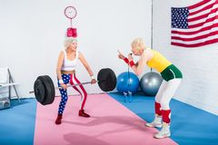 sporty senior woman blowing whistle and looking at elderly sportswoman lifting barbell stock photography
