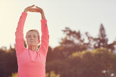 Sporty senior woman doing exercise warm-up stretches outdoors. Senior woman in a pink sporty long-sleeved top stretching her arms above her head, to warm-up for Stock Photo