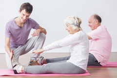 Sporty seniors at fitness studio. Image of sporty seniors with trainer at fintess studio royalty free stock images