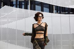 Sporty and brunette fitness model girl with perfect body in stylish sunglasses and military outfit, in camouflage pants and i stock photography