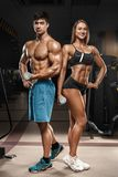 Sporty couple showing muscle and workout in gym. Muscular man and wowan stock photography