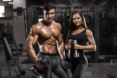 Sporty sexy couple showing muscle and workout in gym. Muscular man and wowan. Sporty sexy couple showing muscle and workout in gym. Muscular men and wowan Royalty Free Stock Image