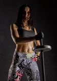 Sporty sexy girl with barbell on a dark background. Athlete doing exercises in the gym. Fitness sexy girl with barbell on a dark background. Athlete doing Stock Images