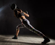 Sporty sexy girl with barbell on a dark background. Athlete doing exercises in the gym. Fitness sexy girl with barbell on a dark background. Athlete doing Royalty Free Stock Image