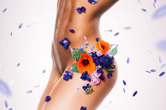 Sporty sexy naked woman body in flowers and petals Stock Photography