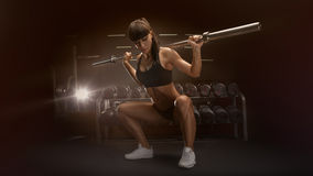 Sporty sexy woman doing squat workout in gym. Sport, bodybuilding, lifestyle concept Fit young woman in great shape lifting barbells looking down, working out in Royalty Free Stock Image