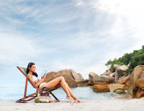 Sporty and sexy woman reading on the beach Royalty Free Stock Images