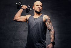Sporty shaved head tattooed male doing shoulder workout with dumbbell. Athletic shaved head tattooed male doing shoulder workout with dumbbell Stock Images