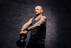 Sporty shaved head tattooed male doing shoulder workout with the Kettlebell. Athletic shaved head tattooed male doing shoulder workout with the Kettlebell Stock Images