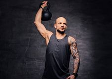 Sporty shaved head tattooed male doing shoulder workout with the Kettlebell. Athletic shaved head tattooed male doing shoulder workout with the Kettlebell Stock Photography