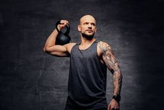 Sporty shaved head tattooed male doing shoulder workout with the Kettlebell. Athletic shaved head tattooed male doing shoulder workout with the Kettlebell Stock Image