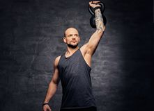 Sporty shaved head tattooed male doing shoulder workout with the Kettlebell. Athletic shaved head tattooed male doing shoulder workout with the Kettlebell Stock Photo