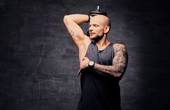 Sporty shaved head tattooed male doing triceps workout with dumbbell. Athletic shaved head tattooed male doing triceps workout with dumbbell Stock Photo