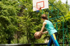 Sporty slender teenager playing basketball Royalty Free Stock Images