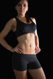 Sporty slender woman posing in sportswear with hands on hips Royalty Free Stock Image