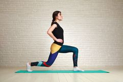 Sporty slim woman doing fitness exercises in studio on brick. Sporty slim woman doing fitness exercises in the studio on a brick wall background Royalty Free Stock Images