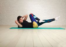 Sporty slim woman doing fitness exercises in studio on brick. Sporty slim woman doing fitness exercises in the studio on a brick wall background Royalty Free Stock Photo