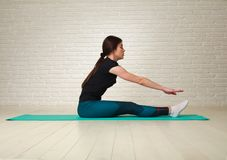 Sporty slim woman doing fitness exercises in studio on brick. Sporty slim woman doing fitness exercises in the studio on a brick wall background Stock Image