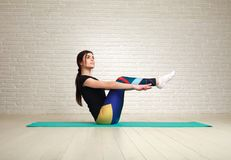 Sporty slim woman doing fitness exercises in studio on brick. Sporty slim woman doing fitness exercises in the studio on a brick wall background Stock Photos