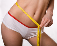 Sporty, slim woman with measuring tape on belly Stock Images