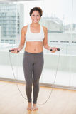 Sporty smiling brunette exercising with skipping rope Stock Images