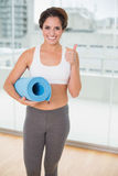Sporty smiling brunette holding exercising mat Stock Photo