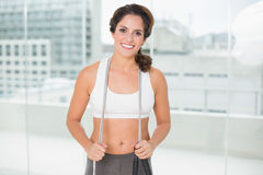 Sporty smiling brunette holding skipping rope Stock Photo