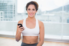 Sporty smiling brunette holding smartphone Royalty Free Stock Photo