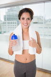 Sporty smiling brunette holding water bottle Stock Photo