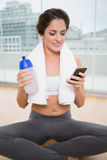 Sporty smiling brunette holding water bottle and smartphone Royalty Free Stock Images