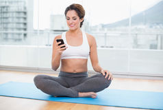 Sporty smiling brunette looking at smartphone Stock Image