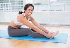 Sporty smiling brunette stretching Royalty Free Stock Images