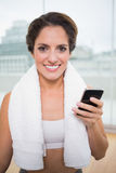 Sporty smiling brunette with towel around neck holding smartphone Royalty Free Stock Image