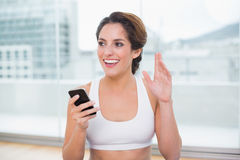 Sporty smiling brunette waving Royalty Free Stock Image
