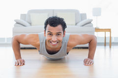 Sporty smiling man doing push ups in the living room. Portrait of a sporty smiling young man doing push ups in the living room at house royalty free stock photos