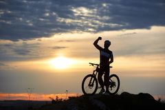 Sporty smiling man stands with bicycle on rock at top of hill against blurred background beautiful sunset stock photo