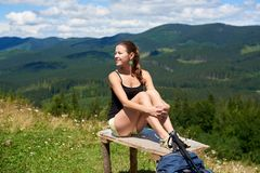 Woman hiker hiking on grassy hill, wearing backpack, using trekking sticks in the mountains. Sporty smiling woman hiker hiking in Carpathian mountain trail stock photos