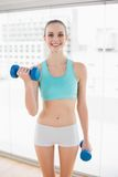 Sporty smiling woman holding dumbbells Royalty Free Stock Photos