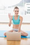 Sporty smiling woman sitting cross-legged in front of laptop waving Stock Photos