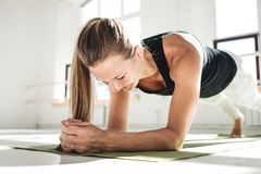 Sporty strong woman doing crossfit workout on yoga mat in sunny gum stock photo