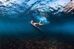 Sporty surfer woman dive underwater with under wave. Sporty surfer woman dive underwater with wave stock photos