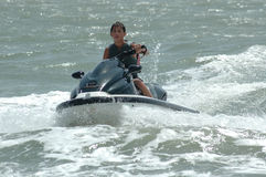 Sporty Teen. A teenage boy rents a wave runner to ride around on the ocean royalty free stock photos