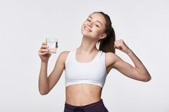 Sporty teen girl with glass of water. In hand showing power gesture Royalty Free Stock Photo