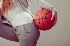 Sporty teen girl holding basketball with one hand. Stock Image