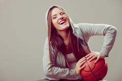 Sporty teen girl in hood holding basketball. Stock Photography