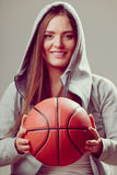 Sporty teen girl in hood holding basketball. Stock Photo