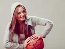 Sporty teen girl in hood holding basketball. Royalty Free Stock Images