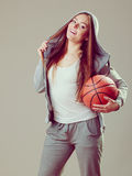 Sporty teen girl in hood holding basketball. Royalty Free Stock Photo