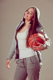 Sporty teen girl in hood holding basketball. Stock Image