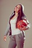 Sporty teen girl in hood holding basketball. Stock Image